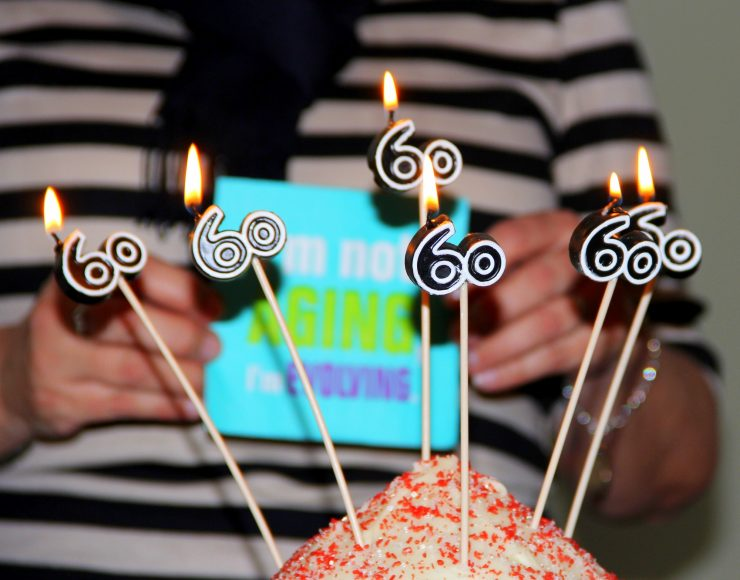 """Woman's 60th Birthday celebration. She is holding a card that reads.""""I'm not aging. I'm Evolving."""""""